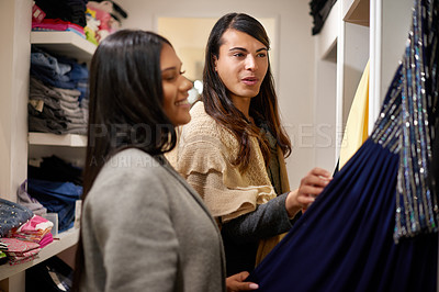 Buy stock photo Cropped shot of two affectionate young friends looking at a dress in a clothing store
