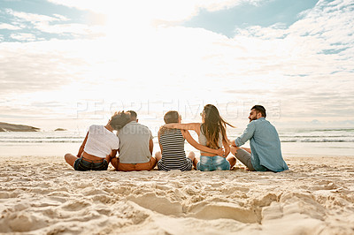 Buy stock photo Rearview shot of a group of happy young friends relaxing together on the beach at sunset