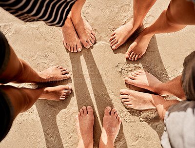 Buy stock photo Cropped shot of a group of friends standing barefoot in a circle at the beach