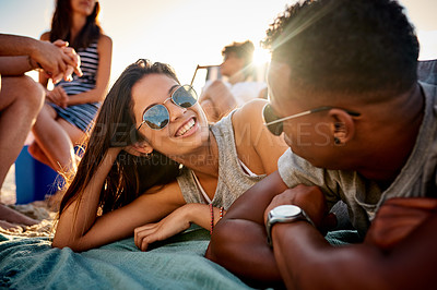 Buy stock photo Shot of a young man and woman chatting while hanging out with friends at the beach