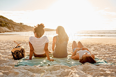Buy stock photo Rearview shot of a group of happy young women relaxing together on the beach at sunset