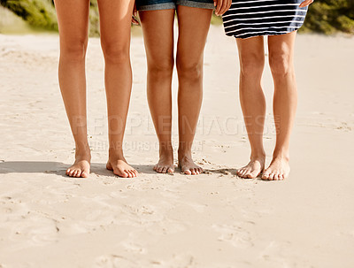 Buy stock photo Cropped shot of a group of friends standing barefoot on the sand at the beach