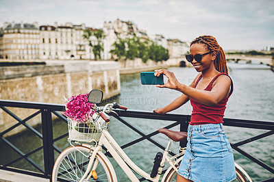 Buy stock photo Shot of a young woman taking selfies while touring the city of Paris with her bicycle