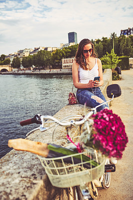 Buy stock photo Shot of a young woman listening to music on her smartphone while touring the city of Paris