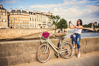 Buy stock photo Shot of a young woman taking photographs with a smartphone while touring the city of Paris