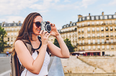 Buy stock photo Shot of a young woman taking photographs with a camera while touring the city of Paris
