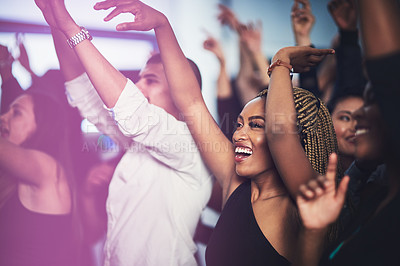 Buy stock photo Cropped shot of an attractive young woman cheering while standing in the crowd at a concert at night