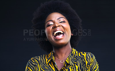 Buy stock photo Shot of a young woman laughing while posing against a dark background