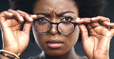 Buy stock photo Cropped shot of a woman adjusting her glasses against a dark background
