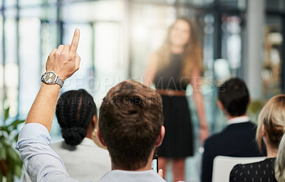 Buy stock photo Rearview shot of an unrecognizable businessman raising his and asking a question at a business conference