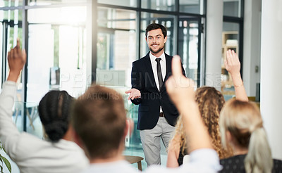 Buy stock photo Shot of a handsome young businessman answering questions at a business conference