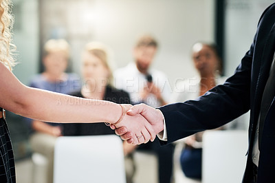 Buy stock photo Shot of two unrecognizable people shaking hands together inside an office with colleagues in the background