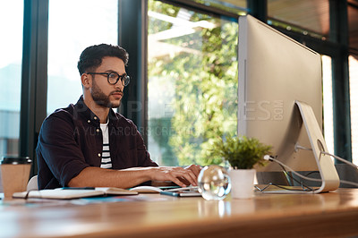 Buy stock photo Cropped shot of a handsome young businessman sitting alone in his office and typing on his computer