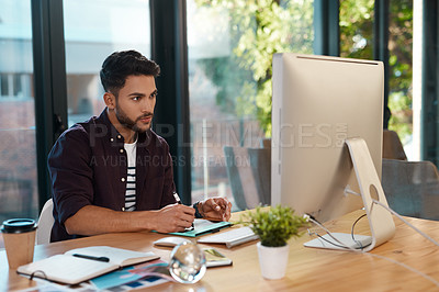 Buy stock photo Cropped shot of a handsome young businessman sitting alone in his office and editing images
