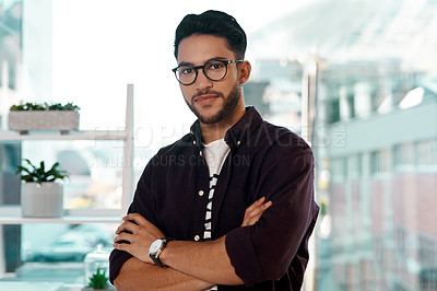 Buy stock photo Cropped portrait of a handsome young businessman wearing spectacles and standing alone in his office with his arms folded