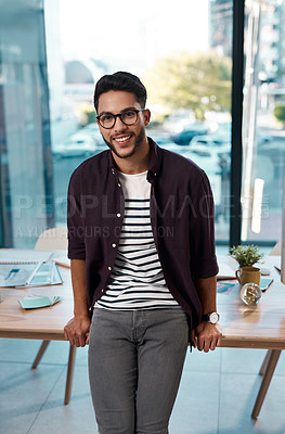 Buy stock photo Cropped portrait of a handsome young businessman wearing spectacles and leaning on his desk while working alone in his office