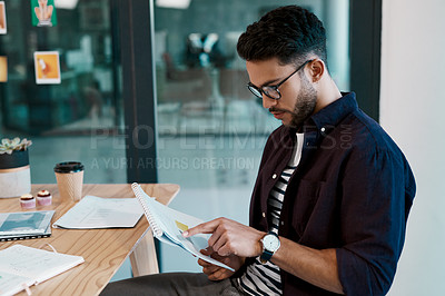 Buy stock photo Cropped shot of a handsome young businessman wearing spectacles and sitting alone in his office while reading paperwork