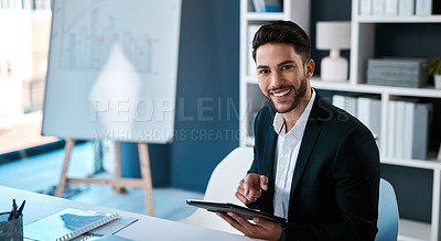 Buy stock photo Cropped portrait of a handsome young businessman sitting alone and using a tablet in his office