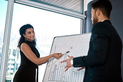Buy stock photo Cropped shot of an attractive young businesswoman standing and using a white board to present data to her male colleague