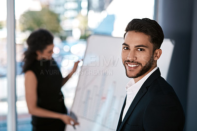 Buy stock photo Cropped portrait of a handsome young businessman standing while his colleague prepares a presentation on a white board behind him