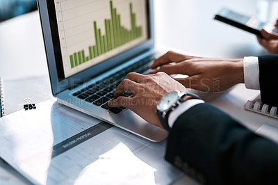Buy stock photo Cropped shot of an unrecognizable businessman sitting with his female colleague in his office and typing on his laptop
