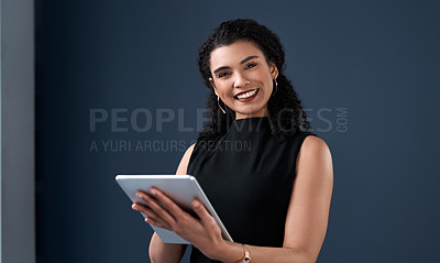 Buy stock photo Cropped portrait of an attractive young businesswoman standing alone and using a tablet against a gray background in the studio