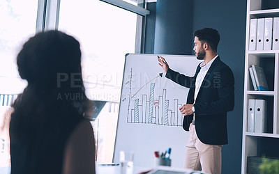 Buy stock photo Cropped shot of a handsome young businessman standing and using a white board to present data to his female colleague