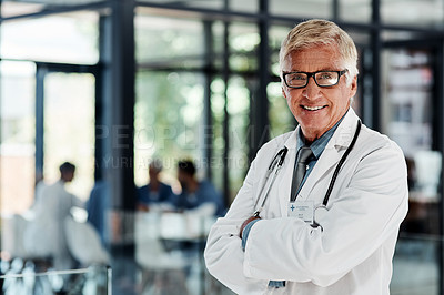 Buy stock photo Portrait of a senior doctor standing with his arms crossed in a hospital