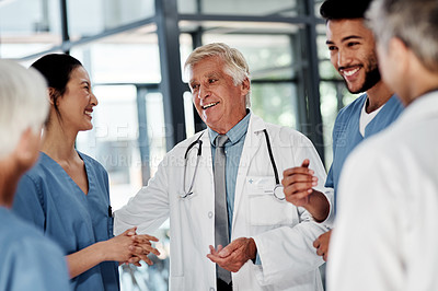 Buy stock photo Shot of a senior doctor having a discussion with his colleagues in a hospital
