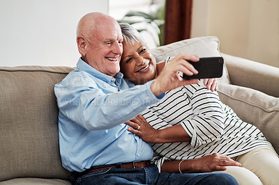 Buy stock photo Shot of a happy senior couple taking a selfie together while relaxing on the sofa at home