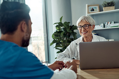 Buy stock photo Cropped shot of an attractive mature female doctor smiling at her male colleague during a meeting in her office