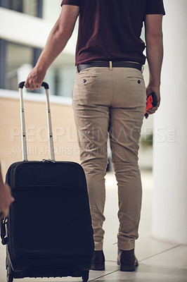 Buy stock photo Rearview shot of an unrecognizable man carrying his luggage in an airport