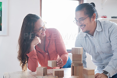 Buy stock photo Shot of a young businessman and businesswoman having a meeting with building blocks in a modern office