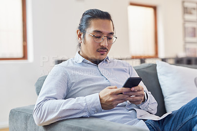 Buy stock photo Shot of a young businessman using a smartphone on a sofa in a modern office