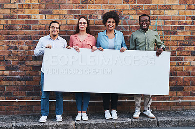 Buy stock photo Shot of a group of young people holding a blank banner against an urban background outdoors