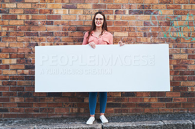 Buy stock photo Shot of a young woman holding a blank banner against an urban background outdoors