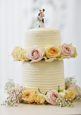 Buy stock photo Shot of a cake topped with plastic bride and groom figurines on a table at a wedding reception