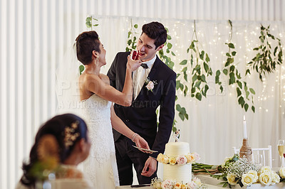 Buy stock photo Shot of a happy young couple tasting the cake at their wedding reception