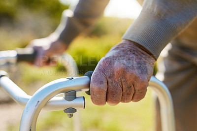 Buy stock photo Cropped shot of an unrecognizable senior man talking a stroll outdoors with the help of his mobility walker