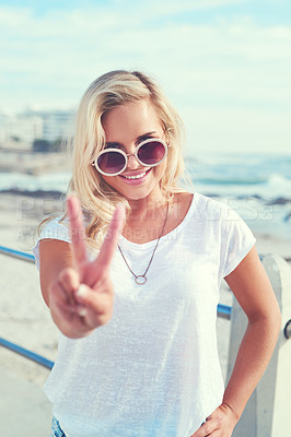 Buy stock photo Shot of a young woman showing the peace sign while standing outdoors on a sunny day