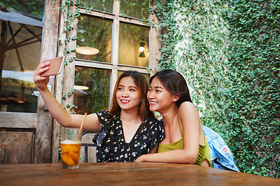 Buy stock photo Shot of two attractive young women taking selfies with a cellphone while relaxing together at an outdoor cafe