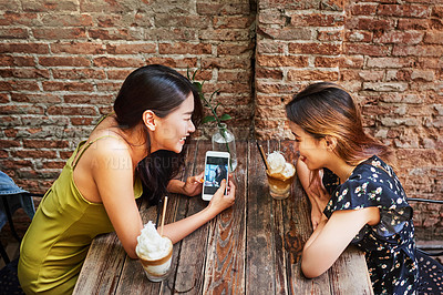 Buy stock photo Shot of two attractive young women using a cellphone while having drinks and relaxing together at an outdoor cafe