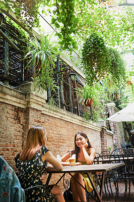 Buy stock photo Shot of two attractive young women having drinks and enjoying themselves at an outdoor cafe
