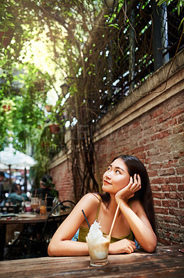 Buy stock photo Shot of an attractive young woman having drinks and enjoying herself at an outdoor cafe