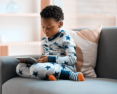 Buy stock photo Full length shot of an adorable little boy using a digital tablet while relaxing on a sofa at home