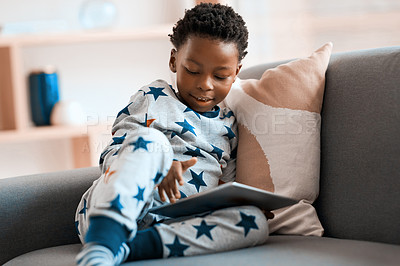 Buy stock photo Shot of an adorable little boy using a digital tablet while relaxing on a sofa at home