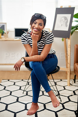 Buy stock photo Portrait of an attractive young artist smiling and feeling cheerful while sitting inside her studio at home