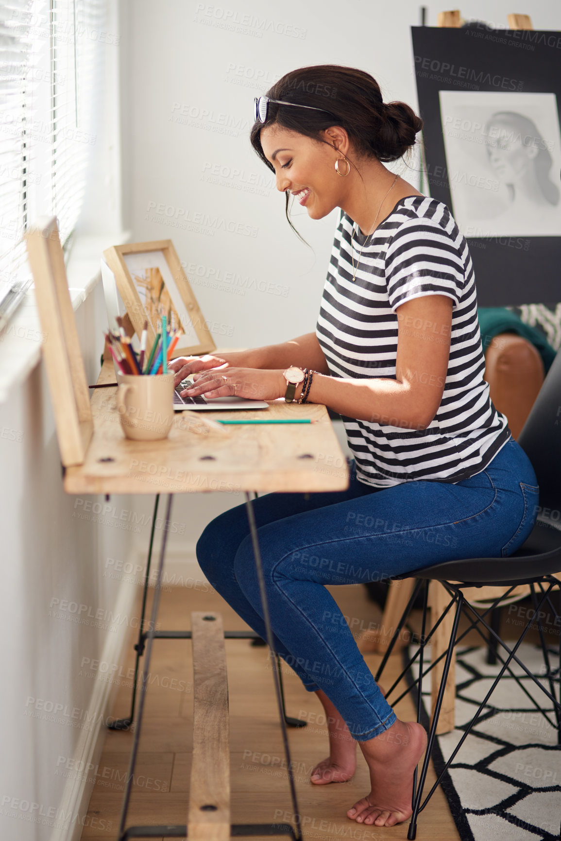 Buy stock photo Full length shot of an attractive and artistic young woman using a laptop while working inside her studio at home