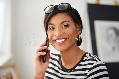 Buy stock photo Portrait of an attractive young artist making a phone call while working inside her studio at home