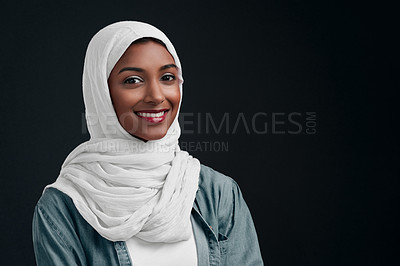 Buy stock photo Cropped shot of an attractive young woman wearing a hijab and standing alone against a black background in the studio